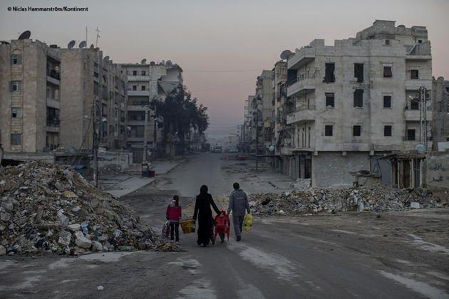 Alepo. Una calle vacía. Edificios derruidos. No hay gente. No hay casas. No hay comercios. No hay nada. No sabemos si esta familia se dirige a otra zona de la ciudad o está abandonando el país. Tal vez las bolsas que llevan son todo lo que les queda. Alepo, la ciudad más grande de Siria, fue en 2006 capital de la cultura islámica. Hoy es un lugar fantasma donde la vida es insostenible (N. Hammarström)