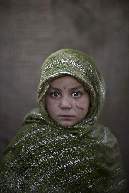 En este Lunes, 27 de enero 2014 de la foto, niña refugiada afgana, Madina Juma, 4, posa para una fotografía, mientras jugaba con otros niños en un barrio pobre en las afueras de Islamabad, Pakistán.  (Foto por Muhammed Muheisen / AP Photo)