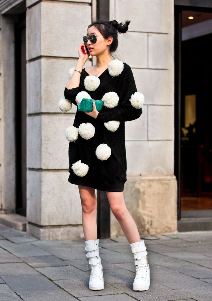 A fun street style look - a black knit covered in cute white pom poms, teamed with a bright green clutch.