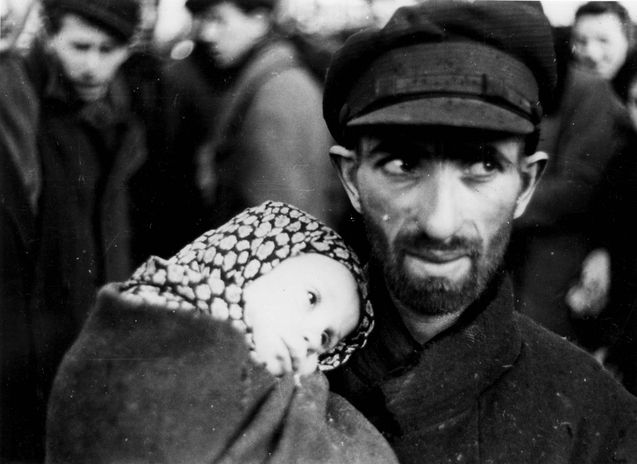 Warsaw, Poland, A man holding a small girl in the ghetto.