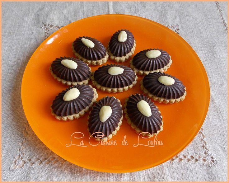 Ingrédients: Chocolats fourrés: - 250g de chocolat noir sans sucre - 115g de chocolat blanc sans sucre - 50g de lait en poudre - 40g de noisettes concassées Pâte à sablés: - 200g de farine complète - 50g de farine de seigle - 55g de noisettes en poudre...