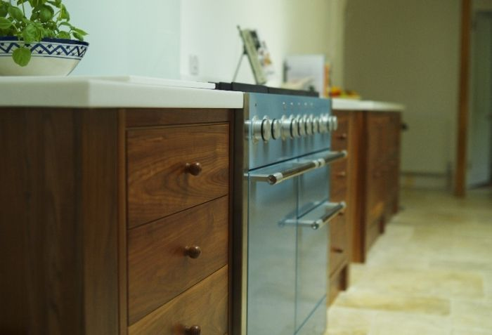 This stylish kitchen from Anthony Mullan Furniture, featuring solid walnut cabinets and light stone surfaces provides the perfect surrounding for this Mercury range cooker.