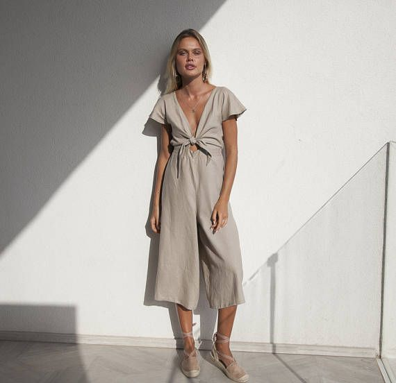 STUNNING- SOFT LINEN - MODERN - JUMPSUIT! MUST HAVE SUMMER PIECE!  Presenting the Ruby Long Linen Playsuit by Palm Collective  Super soft and feminine summer playsuit/ romper / jumpsuit featuring cheeky wide legs, and a colloutte style pant in 3/4 length. The front bodice features a V-neckline and tie front.  Lightweight and easy to wear fabric. Elastic Back for easy fit around the waist to suit different figures.  The tie front also is easily adjustable- so if you are small or large bust…