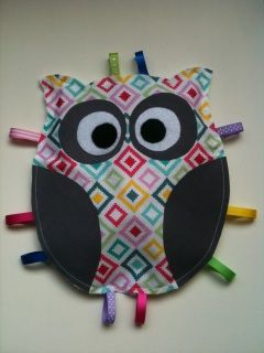 Gorgeous brightly coloured taggy owl with a crinkly inside and a soft minky bobbly back. Gets the sight, sound and touch senses into action!  3 months +  Components: - Cotton fabric - Polyester ribbon - Felt eyes and pupils - Polyester mink/fleece - Fabric fusing - Cellophane inside  Edges will fray slightly with time, but that's all part of the look!