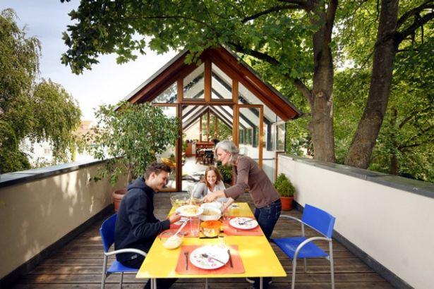 Neubau in schmaler Bauform: Essen unter freiem Himmel auf der schmalen Dachterrasse, dahinter die Teilüberdachung