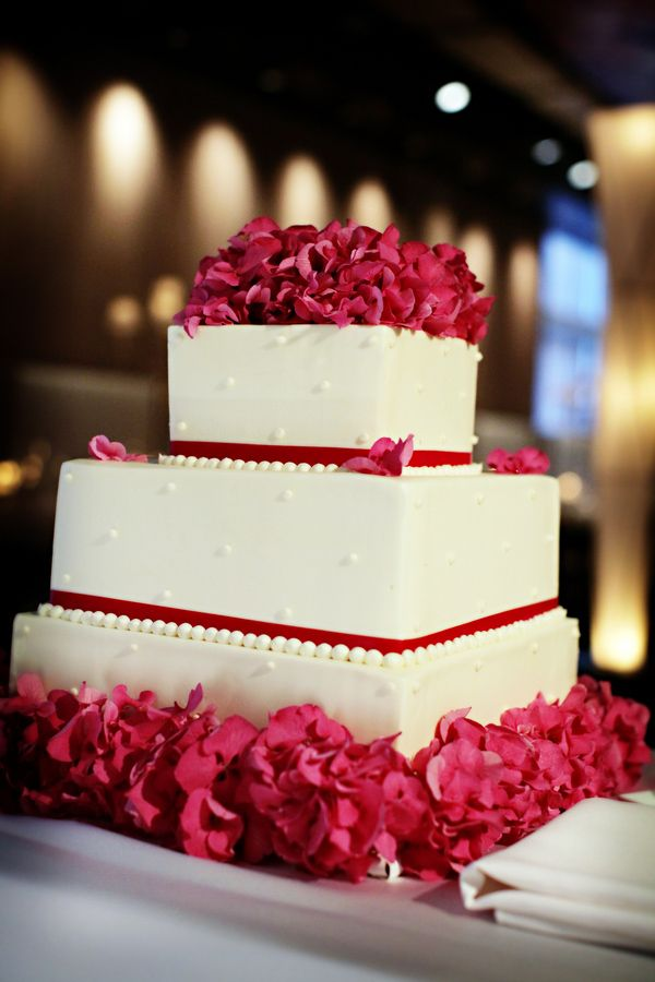 Dark pink accents on three tiered white wedding cake, photo by Chris plus Lynn Photographers