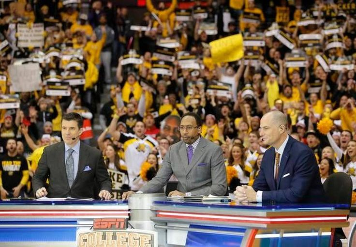 ESPN College Gameday hosts Rece Davis, Stephen A. Smith and Jay Bilas sit at a desk at mid-court during the show's live broadcast from Koch Arena Saturday morning.