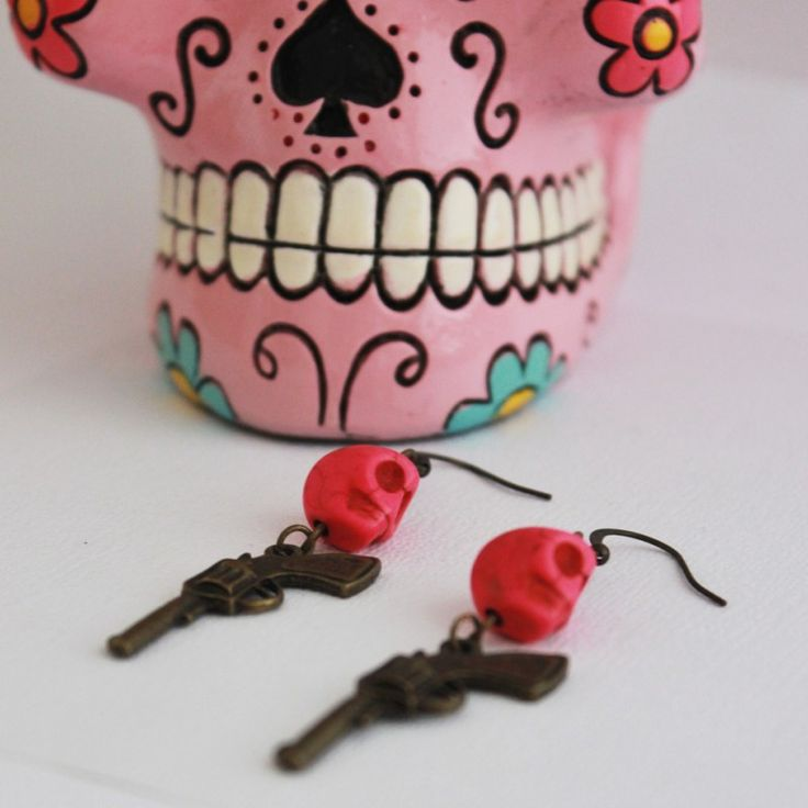 Day of the Dead Sugar Skull and Pistol Earrings Head 'South of the Border' with these fun earrings featuring Day of the Dead sugar skulls and rockabilly pistols! Antique gold coloured pistol charms measuring approx. 24mm In length dangle from bright pink howlite sugar skulls which are attached to French hook earring wires.  AUD $16.00 (Free Postage within Australia)