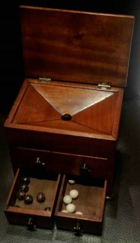 1740-60 ca. Ballot Box Used by gentleman`s private club or secret society. Miniature lidded chest, full plus two half-drawers, mahogany, Dutch drop brass handles, four brass feet. Lid lifts to chamfered top with hole. Ball dropped, lid gave privacy so fellow members unable to see colour selected - white if supporting candidate, black if not. After votes cast, top drawer opened. If all white, candidate elected. If `blackballed`, forbidden membership or not granted post. fisher-london.com