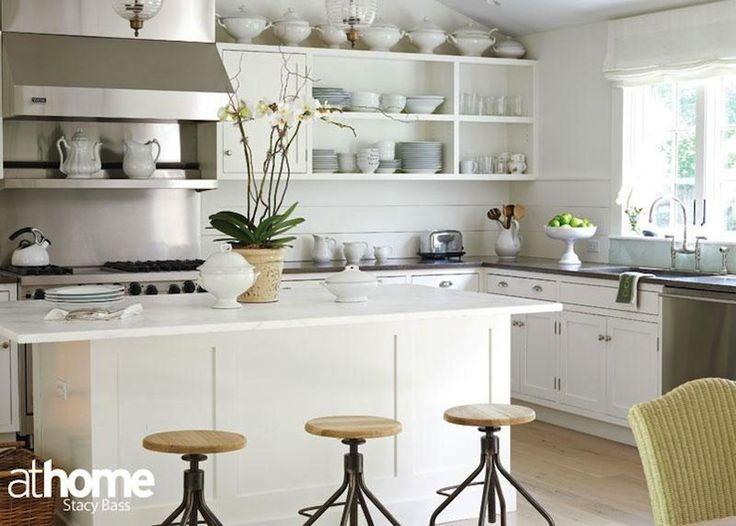 L shaped cottage kitchen design with white wood paneled walls and oak hardwood floors.