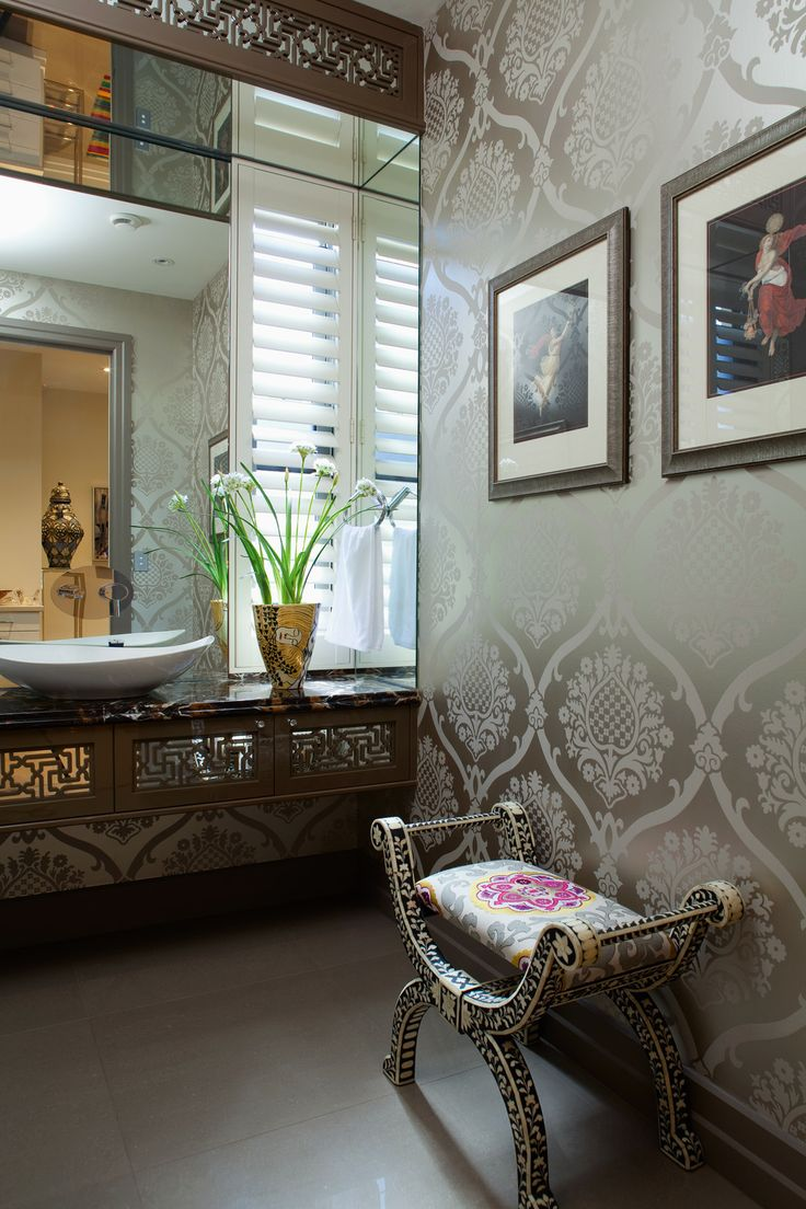 Powder room with custom designed cabinetry featuring laser-cut detail, Designers Guild wallpaper and a bone-inlay stool upholstered in an embroidered Suzani style fabric.