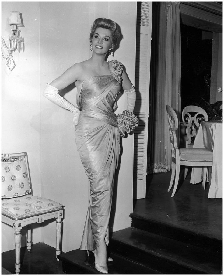 American actor Donna Douglas posing in a formfitting, draped, silk gown, designed by Walter Plunkett, while promoting director Vincente Minnelli's film, Bells Are Ringing - 1960