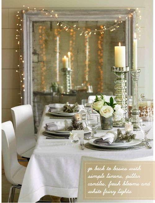 an over-sized mirror with a strand of lights draped over it adds such a romantic feel to a dining room