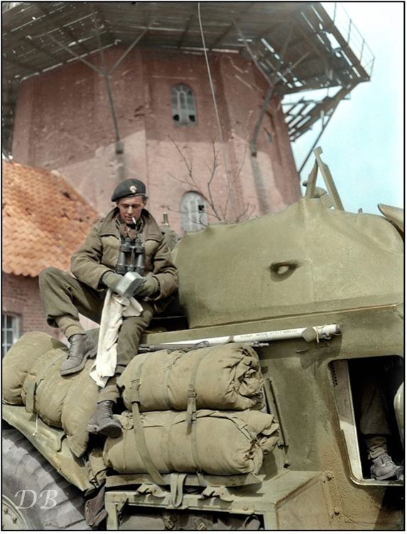"""Sergeant I.F.Chase cleaning his mess tin on a General Motors T17E1 Staghound armoured car of the South Alberta Regiment, 4th Canadian Division, Bad Zwischenahn, Germany, 29 April 1945 """