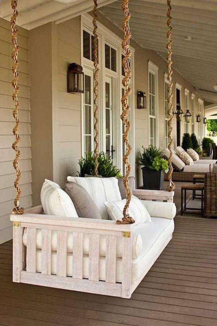 Luxe witte schommel hangbank onder een dak in de tuin. Met een paar dikke kussens is het een heerlijke hangplek. Dit is eventueel ook zelf te maken.