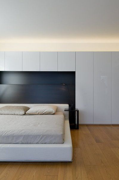 Storage space with indirect lighting in black white and wood bedroom in a Moscow Apartment by Alexey Nikolashin