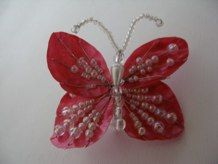 """Mariposa en escamas de pescado de 2 ½""""de ancho en rojo con detalles de perlas en las alas.<br />"""