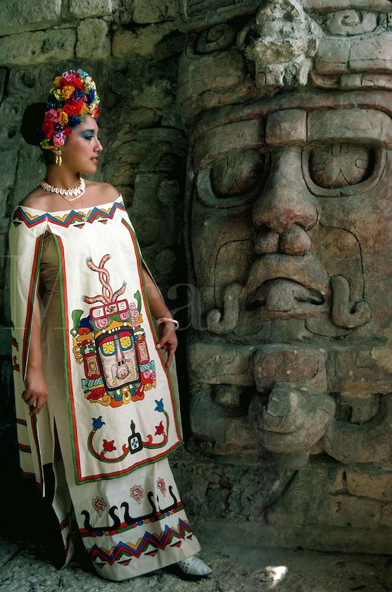 Young woman in Mayan dress posing by statue of Sun God at Mayan ruins of Kohunlich. Yucatan, Mexico.