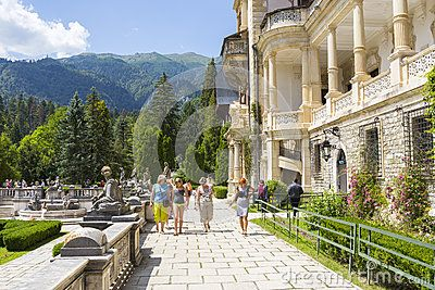 Unidentified group of tourists stroll down the alleys of Peles castle garden on July 24, 2013 in Sinaia, Romania. Peles castle was declared museum in 1953 and is the most visited in Romania with more than 300.000 tourists every year.