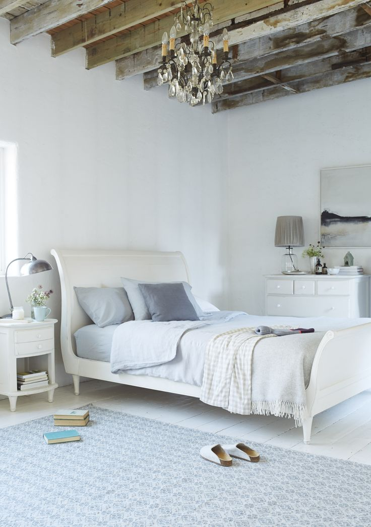 Loaf's off-white Lauren sleigh bed with a lightly scuffed wooden headboard and footboard in this all white bedroom