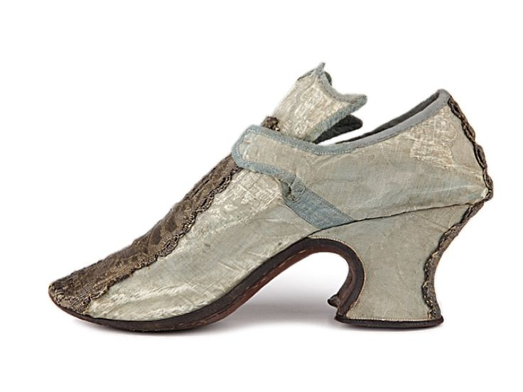 Lady's light blue damask shoes with short straps for bow ties and high tongue with zig-zag edge.    Great Britain. c. 1710-1720