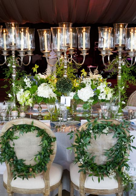 The bride and groom's chairs decorated with vines and flowers.