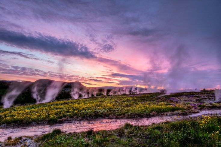 A purple and pink sky reflected in a stream at sunset while hot springs vent steam into the air in Iceland, the land of ice and fire.