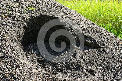 Hole in the pile of cement on grass.