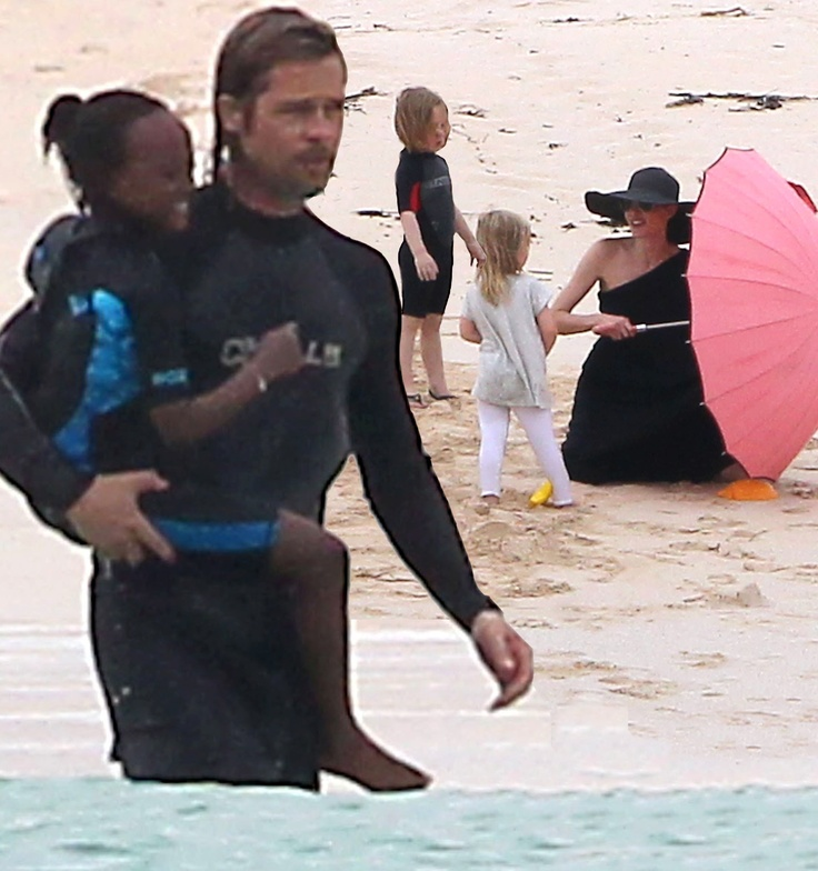 Brad Pitt with daughter Zahara while wife Angelina Jolie plays with their other daughters Shiloh & Vivienne on shore