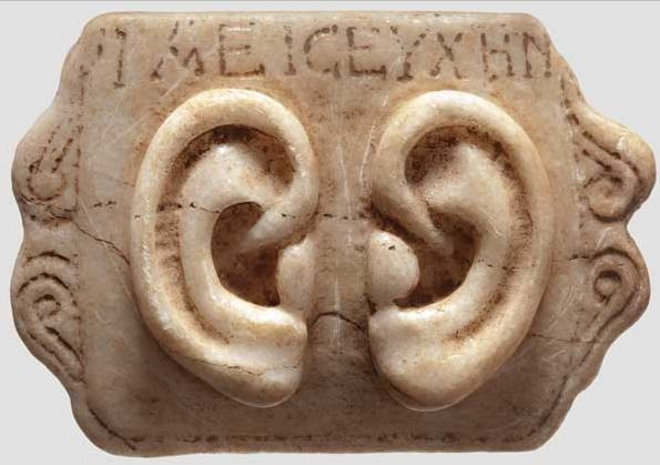 "Roman Votive Ear Panel, 1st-3rd century AD.   Made from marble with a Greek inscription """"IAEICEYXHN""""(?).  Votive offerings were presented to a god, sometimes either in the hope of a cure or as thanks for one. They were made in the shape of the afflicted body part – in this case a person's ears so the owner of these ears may have had hearing problems or an ear infection. Ear votives may also have been given in the hopes that the god may ""listen"" to their requests in earnest."