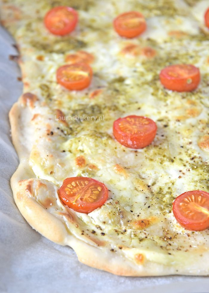 Deze caprese flammkuchen heeft een Italiaanse twist gekregen door de pesto, tomaat en mozzarella topping. Een heerlijke variatie op de bekende klassieker.