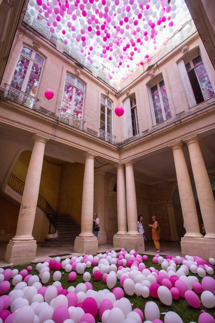 """Nestled within a courtyard at the Hôtel de Griffy in Montpellier, France, this 2015 installation of pink and white balloons attempts to capture the feeling of spring by mimicking the color and feel of cherry blossoms as they fall from the ceiling. The 6-day installation titled """"Un dixième Printemps"""""""