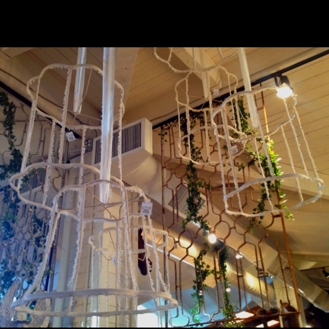 Old lamp shades ripped and frayed hanging from ribbon. Cute and totally DIY capable.
