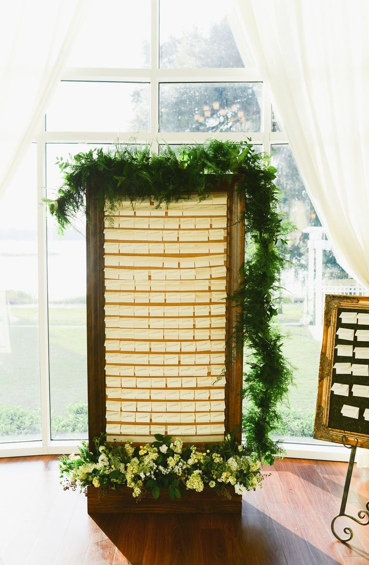 a beautiful varnished wood place card display board mimics a doorframe set in a lush and full flower box. Cards are folded over a double faced satin ribbon placed in alphabetical order making it easy for guests to find their name and table number.