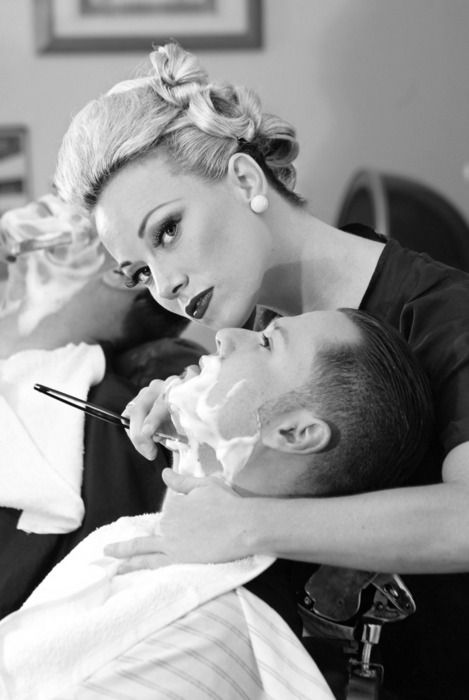 Female barber giving a shave. I would like to have a female barber who has her style work in my shop. I would like the male barbers to have tradition cuts and facial hair. I personally have a slick back hair do.