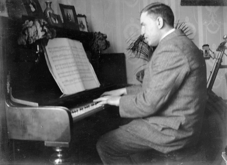 Digital image, copy of a glass plate negative, from a collection of family photographs lent by Alexander Downie depicting a man playing piano in a family sitting room c.1910-1920