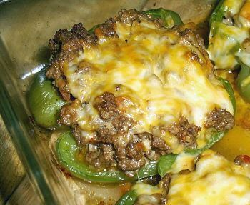 Lo carb Stuffed Peppers  2 large green peppers, halved lengthwise   1 pound ground beef   1/4 cup onion, chopped, 1 1/4 ounces   1 clove garlic, minced   1/2 cup tomato, chopped, about 2 ounces   Salt and pepper, to taste   4 ounces cheddar cheese, shredded   2 ounces cheddar cheese, shredded, for topping