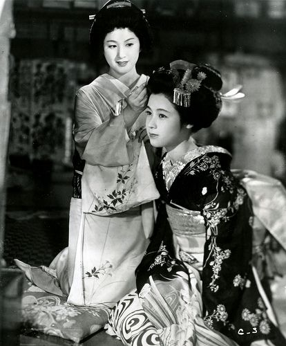 Gion Bayashi (1953) Michiyo Kogure as Geiko Miyoharu in the background and Ayako Wakao as Maiko Miyoei in the foreground, who is shown here, being dressed for her Misedashi (debut as a Maiko).