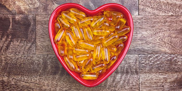 Some cod liver oil supplement capsules in a heart shaped dish