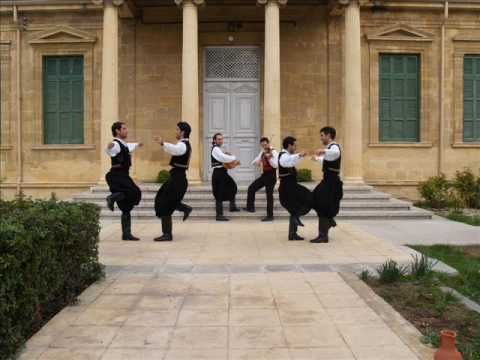 """Vraka is a dance done to the popular Cypriot song """"Η Vraka."""" The lively, cheerful song of this antikrιstos (face to face) dance is centered on a piece of the traditional men's dress, the Cypriot Vraka. It is a variation of the song """"Koniali"""" which originated in Ikonion, Asia Minor & has lyrics in Greek, Cypriot Greek, Cappadocian Greek, Turkish, and Karamanlidika. This piece of music traveled throughout the Greek-speaking world by refugees since it was beloved by musicians, artists, and…"""