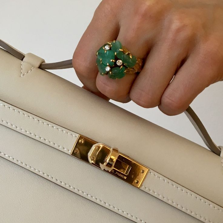 Diamond, gold and carved emerald ring by Afro Basaldella, and Hermes Craie Swift leather Kelly pochette.