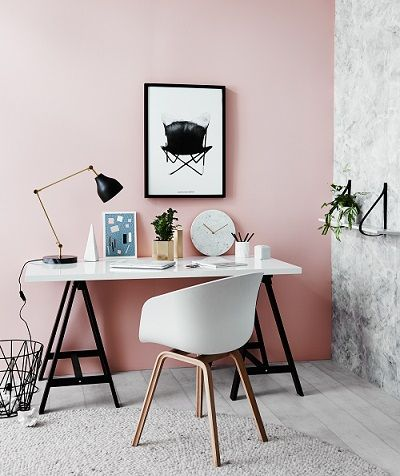 Pink paint on walls. Sawhorse desk, white eames shell chair for a touch of mid century modern