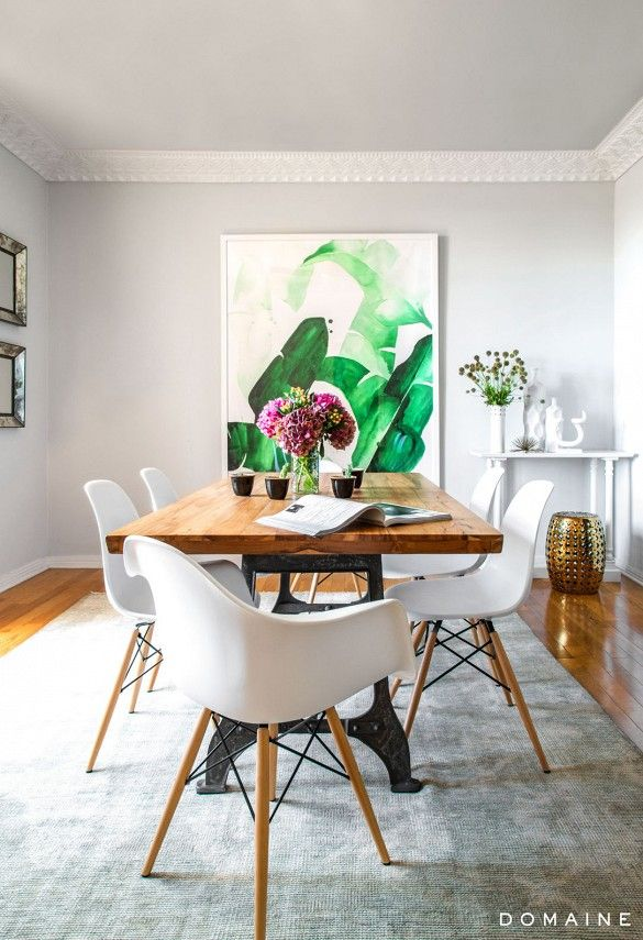 Exclusive: Tour Margo & Me's Hollywood Haven | DomaineHome.com // A palm art print serves as a backdrop for a rustic wooden table and Eames dining set.