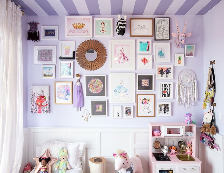 A stunning art gallery wall in a purple toddler room with pieces by Minted and The Land of Nod.