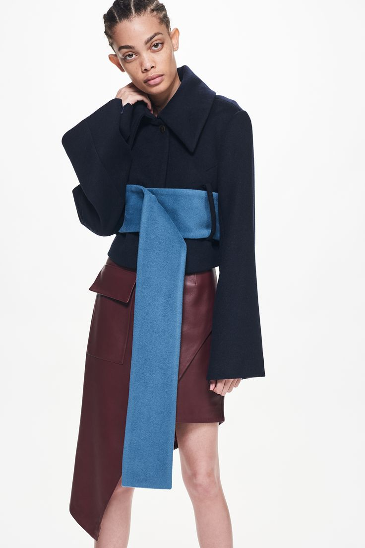 Ji Oh Navy Wool Cropped Oversized Collar Jacket With Elongated Belt Flared Sleeves With Zippers Button Closure And Burgundy Lambskin Asymmetrical Knee Length Mini Skirt With Side Cargo Pocket