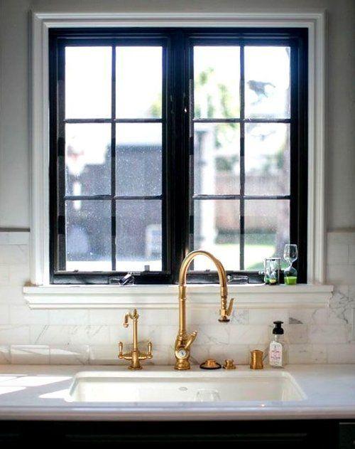 Black window frames, white surface, brass taps
