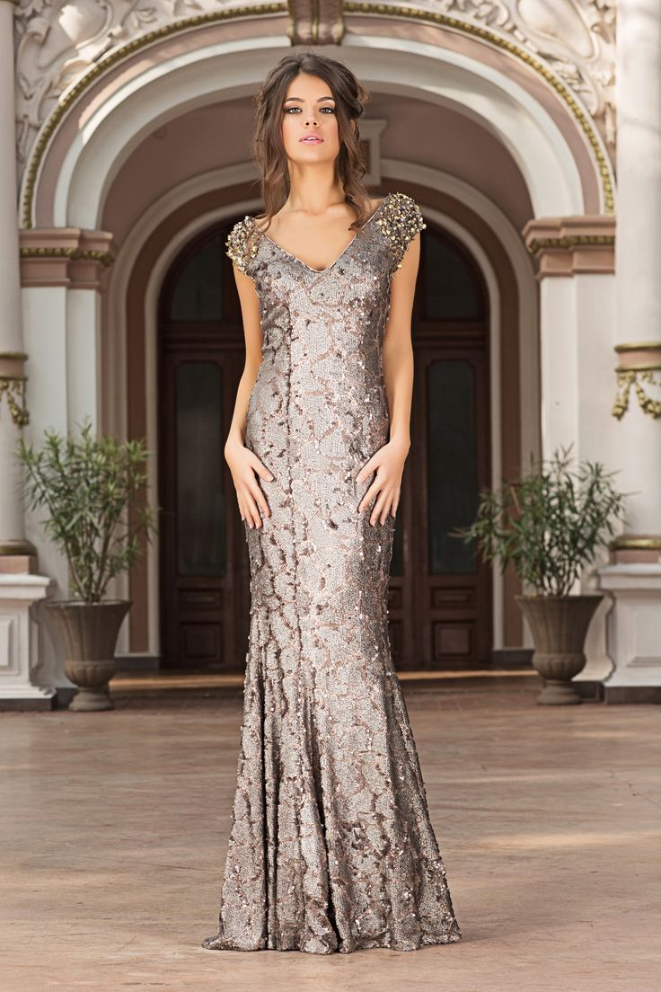 Sparkle and glow in this exquisite evening dress from Vero Milano!A unique long sequin dress with a low V-neckline and a glamorous train. Simply stunning!