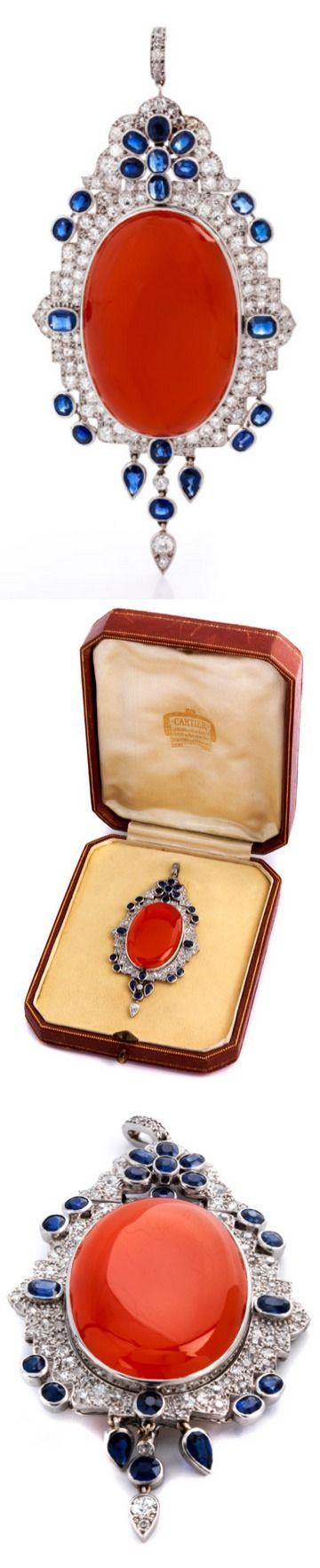 """Carnelian, diamond and sapphire pendant by Cartier - Yellow gold and platinum. Signed """"Mtd Cartier"""". Ca. 1930. Highly decorative, exceptional brooch or pendant with central, large flat cabochon-cut carnelian sun (with closed true-foiled back), approx 3.8 cm x 2 cm, with a surround of Fine cornflower blue oval and drop shaped facetted sapphires, altogether approx 6:10 CT, and old-cut diamonds, altogether approx 4:10 CT.:"""