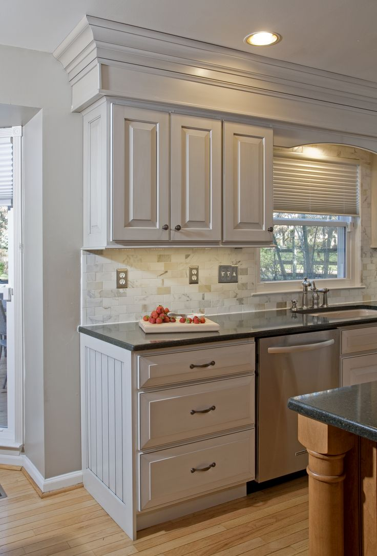 """The Veneto finish pulls out the warm gray tones in the new 2"""" x 3"""" marble backsplash.  The cabinet ends are finished with wainscot panels and bead board."""