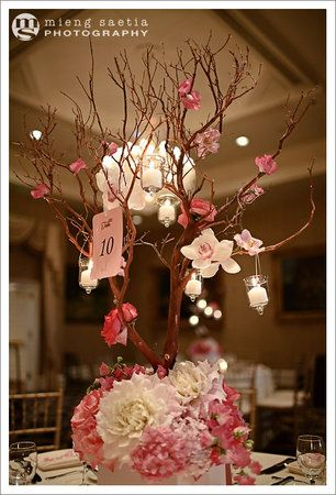 Center pieces with branches with apple blossoms and tissue paper for flowers on the bottom